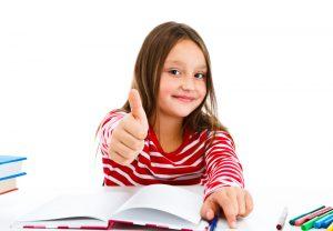 Dziewczynka siedzi przy biurku z otwartym zeszytem i pokazuje kciuk do góry w znaku OK.