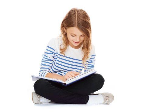 Dziewczynka czyta książkę z radością.