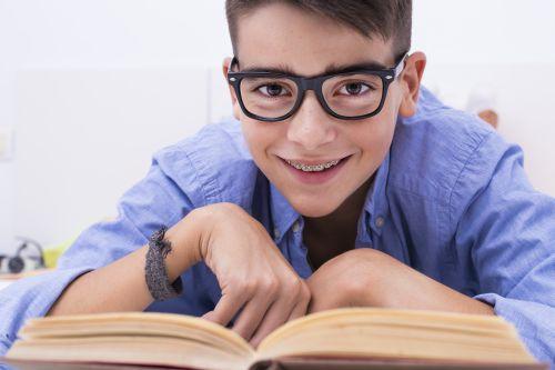Chłopiec w okularach czyta książkę z uśmiechem.