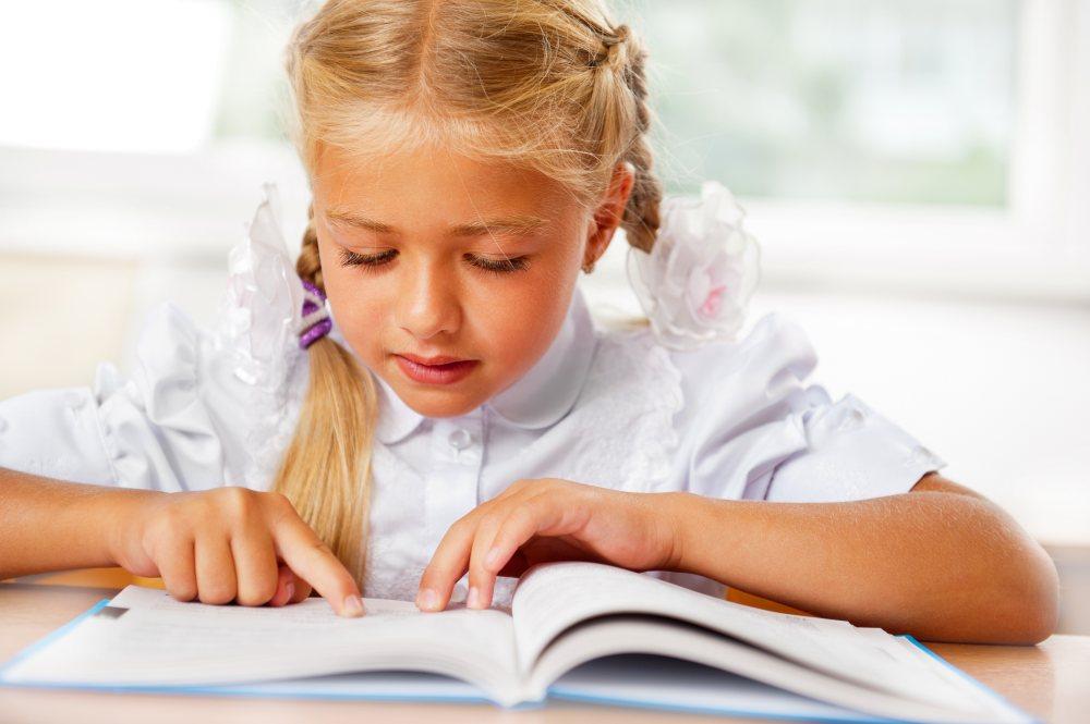 Mała dziewczynka uczy się czytaćę czytać.