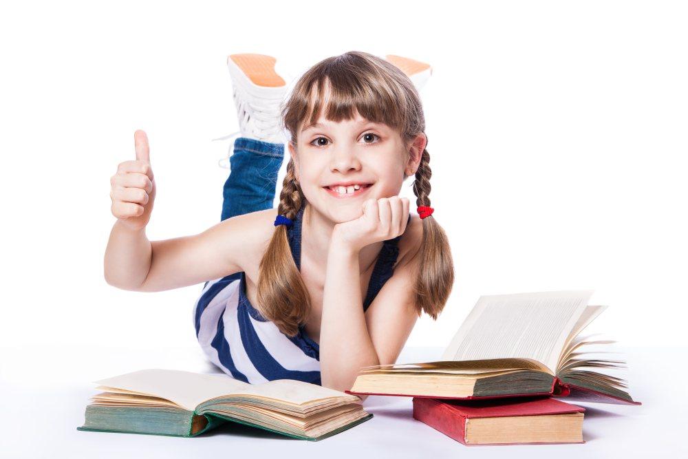 Dziewczynka leży przy książkach i pokazuje kciuk do góry w znak OK.
