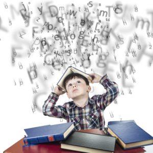 Chłopiec siedzi przy biurku z książkami, spadają na niego litery.
