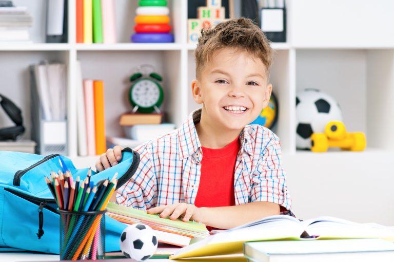 Uśmiechnięty chłopiec wyciąga książki z plecaka na swoim biurku.