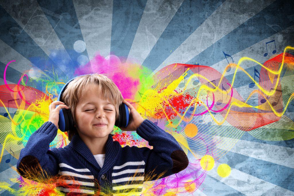 Chłopiec ma zamknięte oczy, a na uszach słuchawki, z których wydobywają się kolorowe, muzyczne fale.