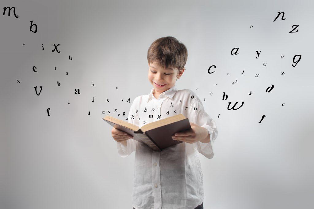 Chłopiec trzyma w rękach dużą książkę, z której wylatują litery.