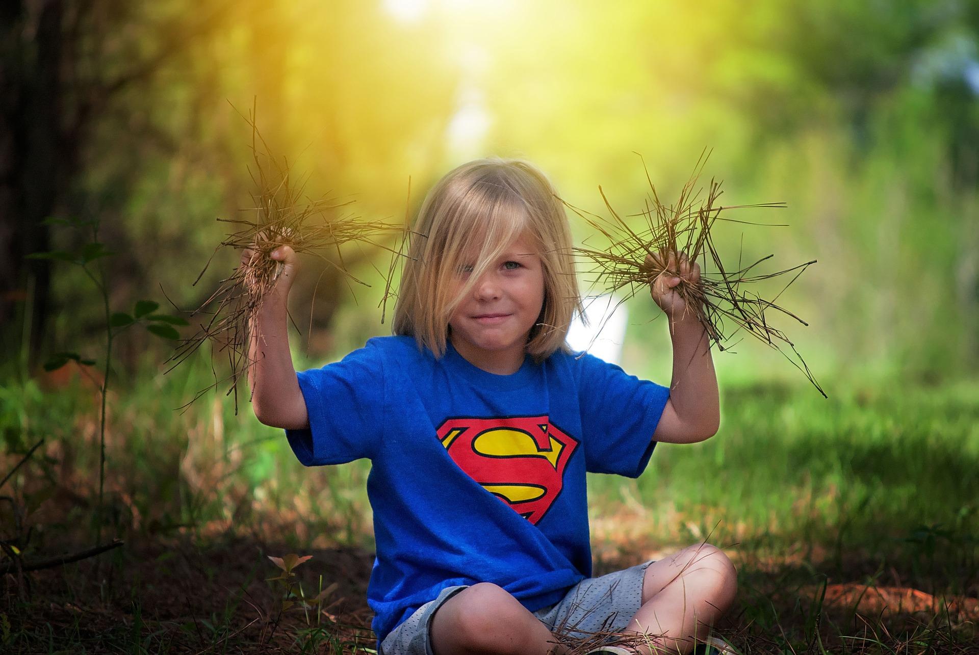Dziecko siedzi na dworze na trawie i trzyma w rękach wyrwane z ziemi rośliny.