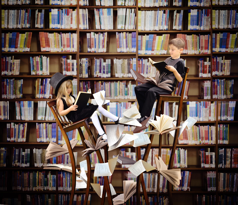 Chłopiec i dziewczynka siedzą na wysokich krzesłach w bibliotece, czytają książki, a wokół nich latają kartki.