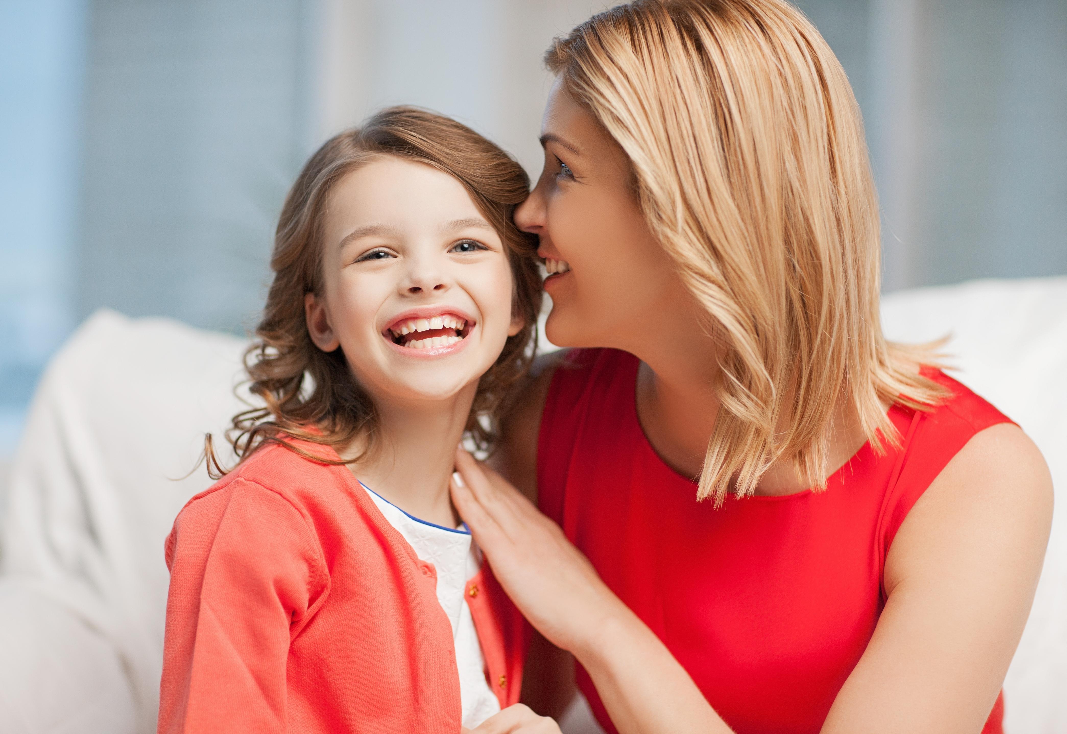 Mama szepcze swojej córce na ucho, a córka się śmieje.